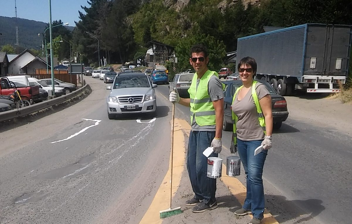 Un vecino y una vecina pintan los baches de las rutas como prevención y denuncia